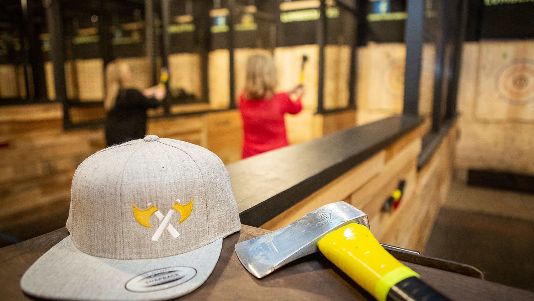 Axe throwing range with gray hat and axe