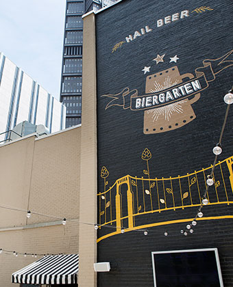 The Biergarten Rooftop Bar Pittsburgh Mural. Rooftop Biergarten with views of the city. Dangling Bulbs and outdoor TVs.