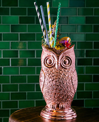 Copper Plated Owl Chalise with colorful paper straws, and flower garnish cocktail against a green brick wall